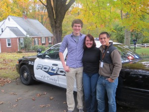Beth, Christian, and Chris in front of the police car
