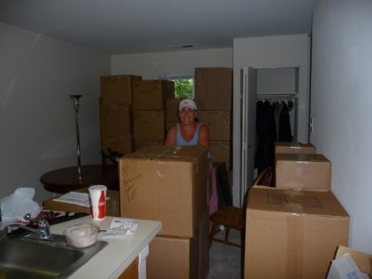 Beth surronded by boxes in the Kathy Stree Apartment