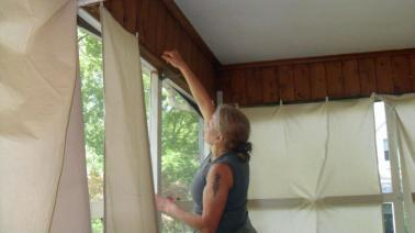 Maria hanging up the new window coverings she made